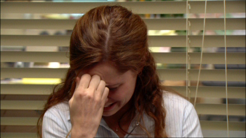 Pam from the office, looking down with her hand on her forehead