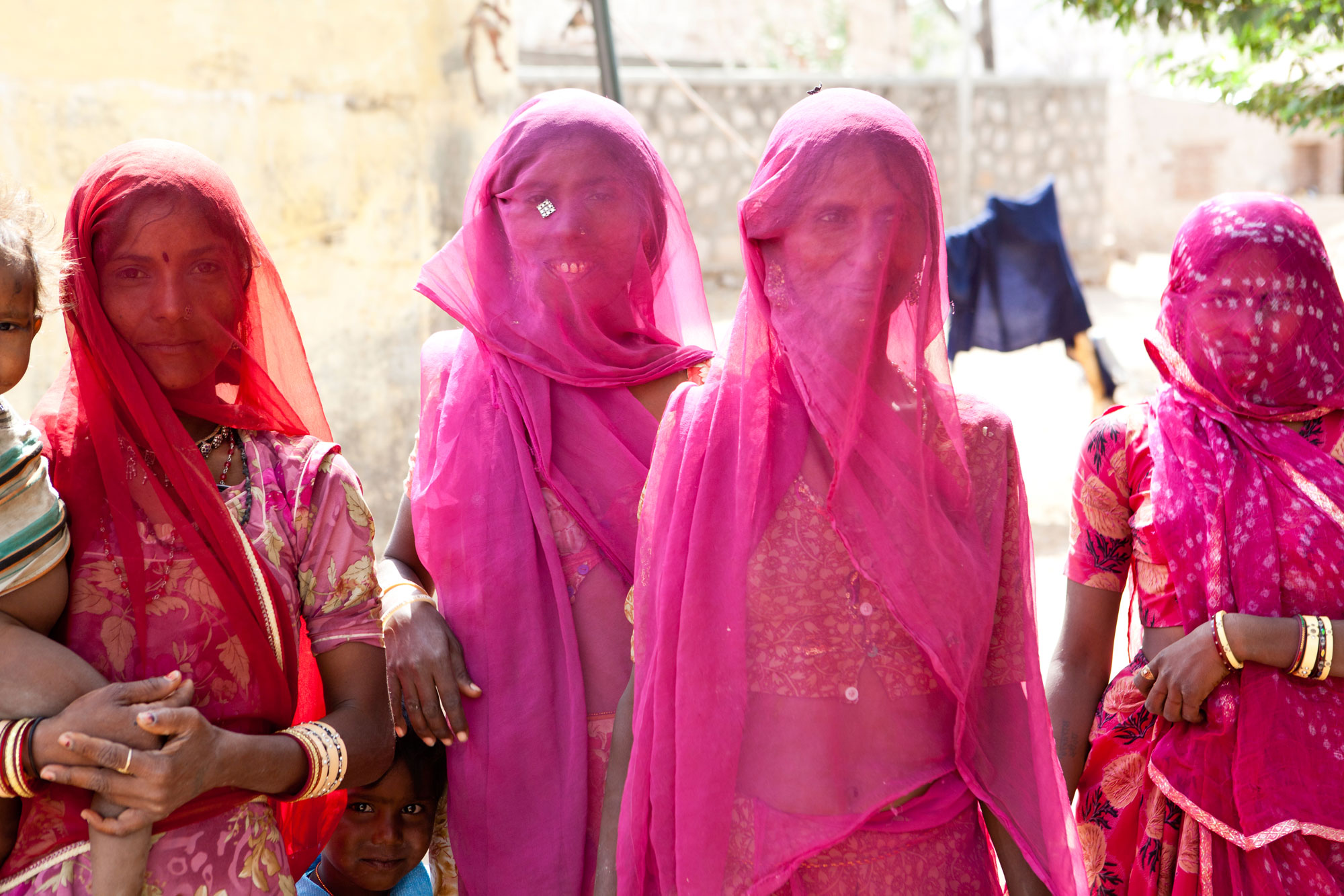Girls in a village wearing pink sarees, standing in a line