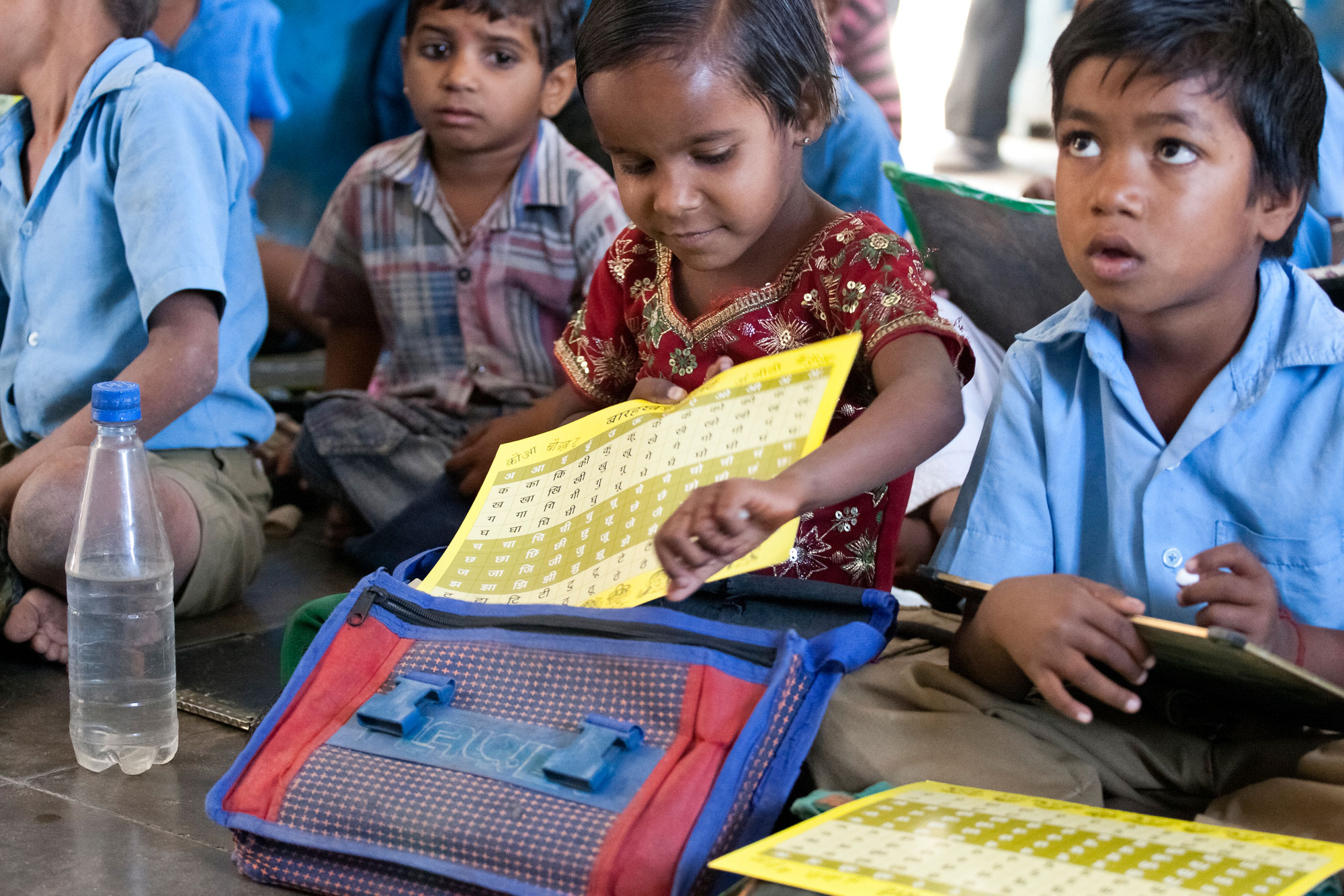 A young underprivileged girl keeping her Hindi sheets inside her bag