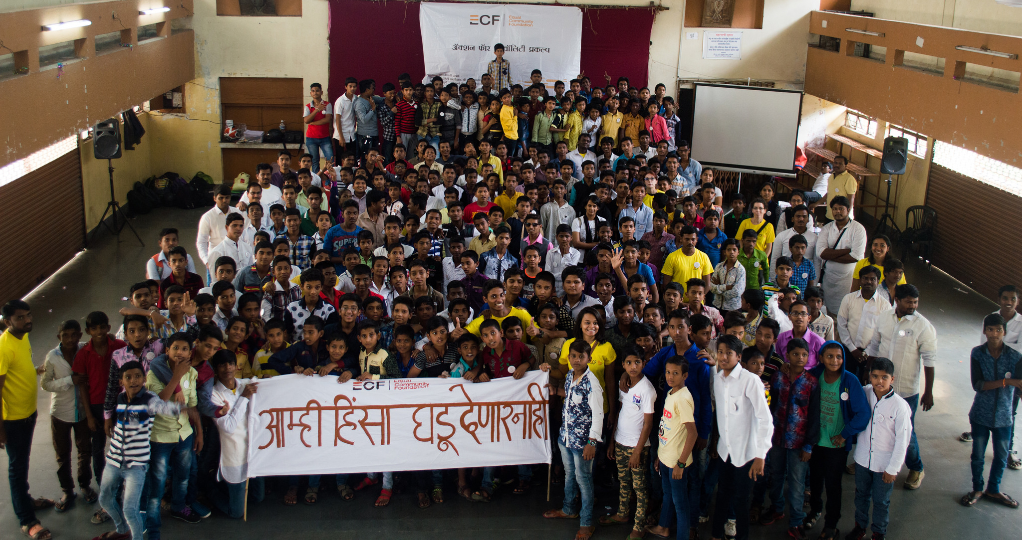 ECF young boys and men standing in a group with a banner - prevention of violence against women