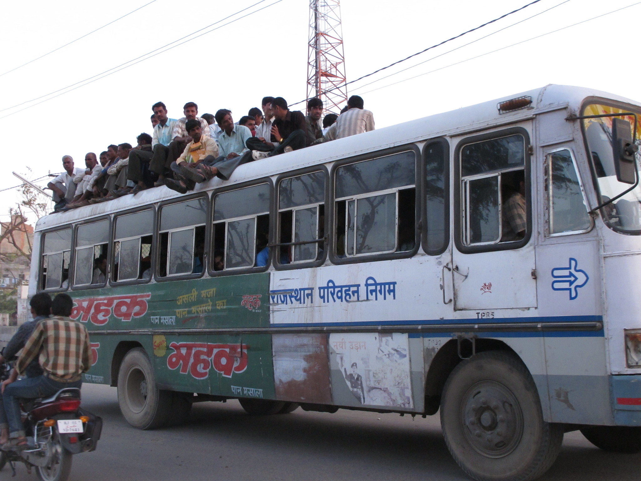A crowded bus in India with people sitting on the roof