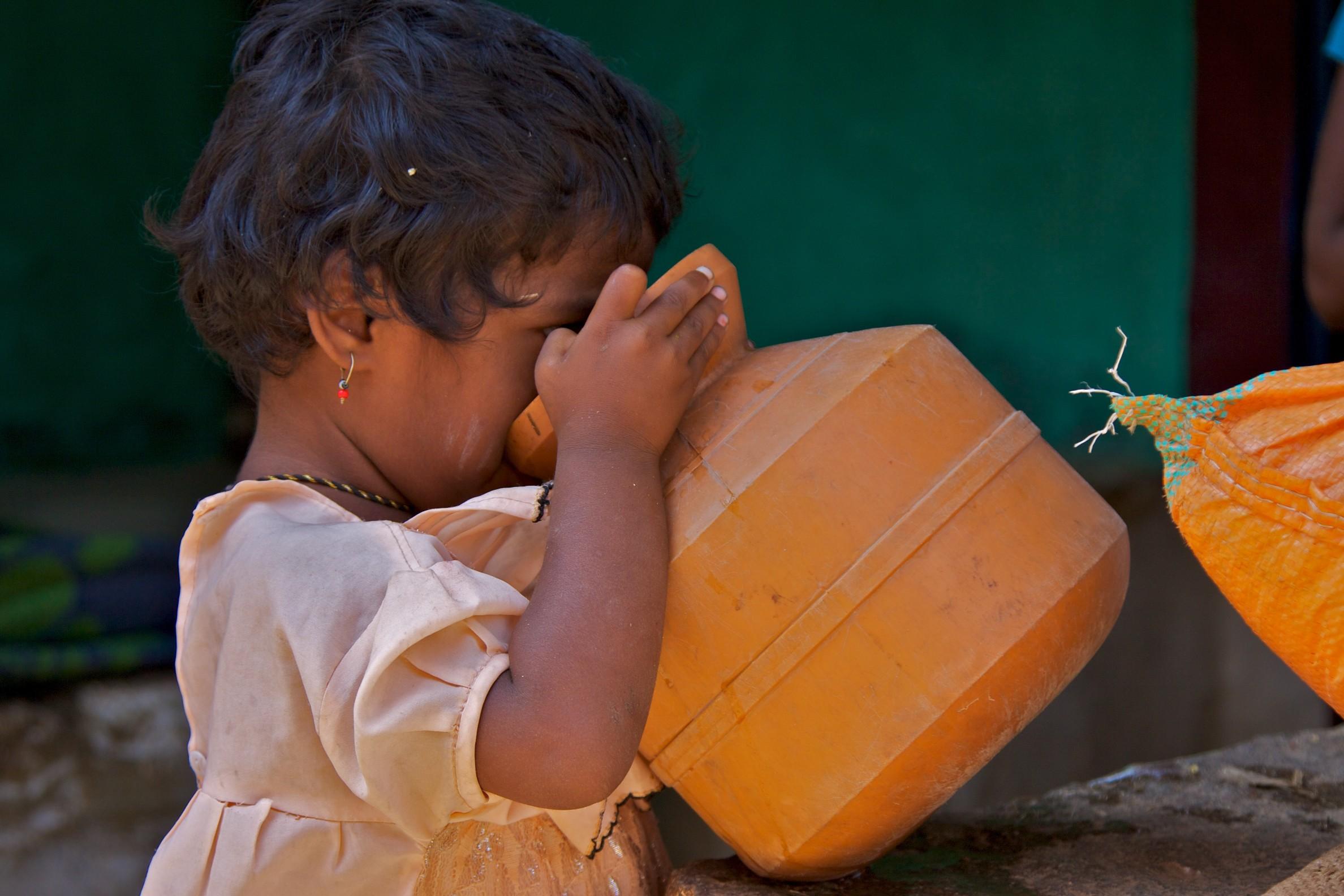A girl drinking water from an earthen pot_ASwaminathan