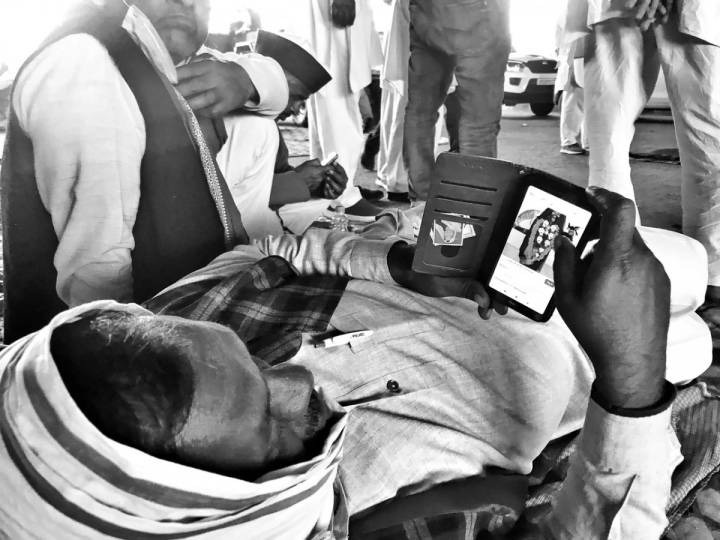 A man lying down with his head covered with a cloth looking into his mobile phone-farmers protest