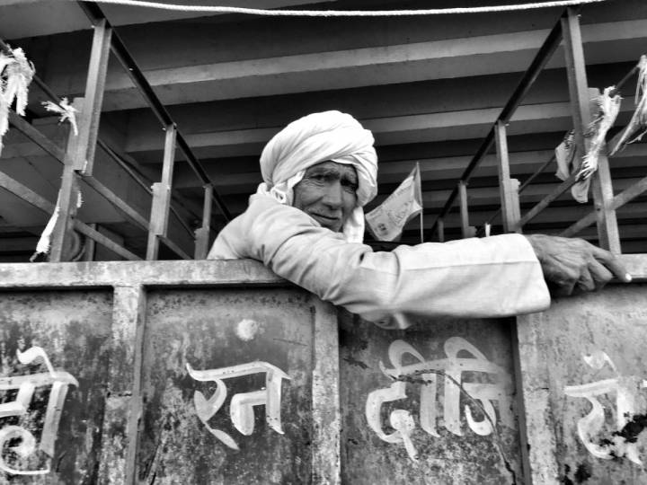A man wearing a turban sitting inside a truck looking outside into the camera-farmers protest