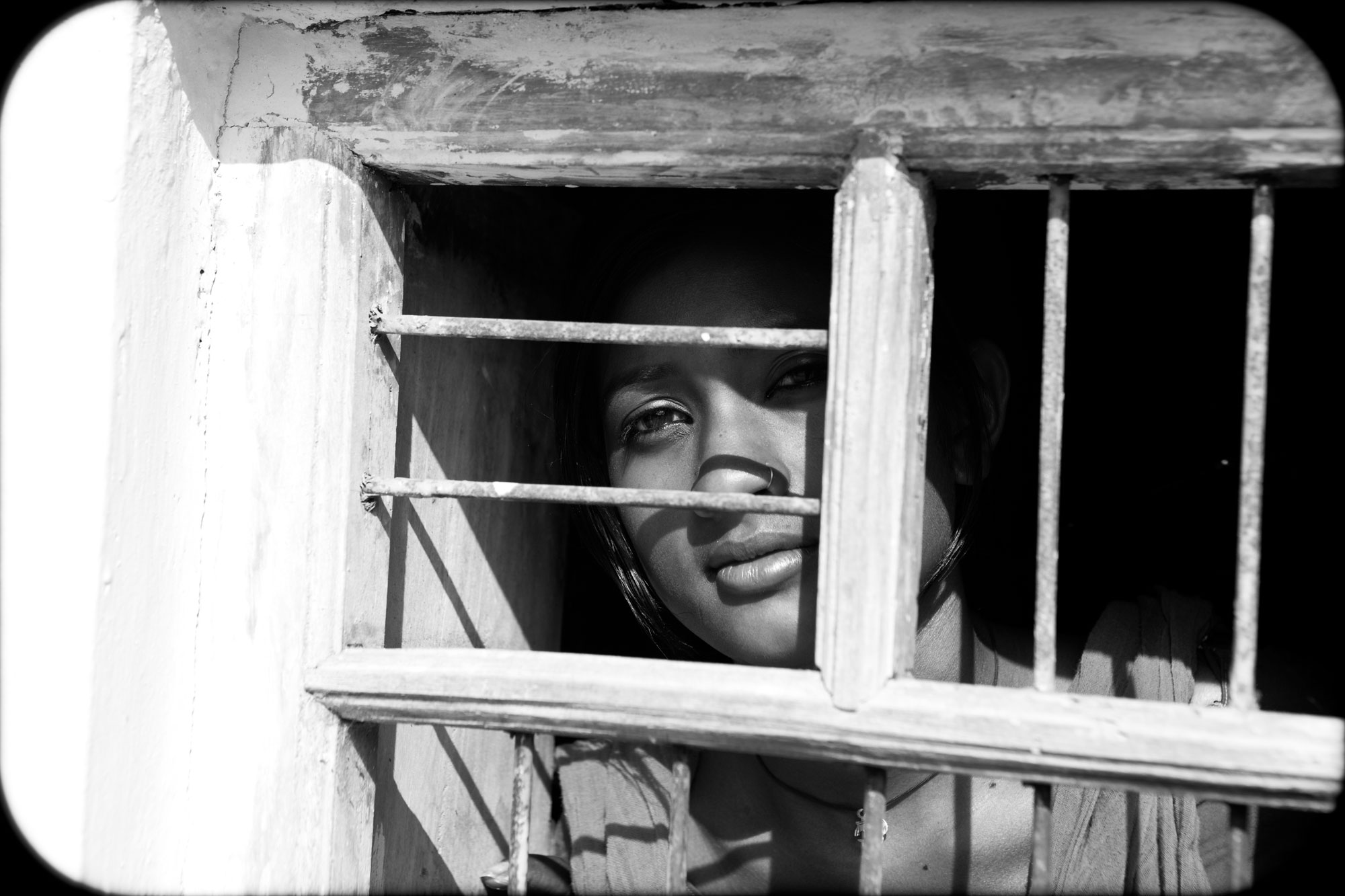An Indian woman looking out from behind window bars