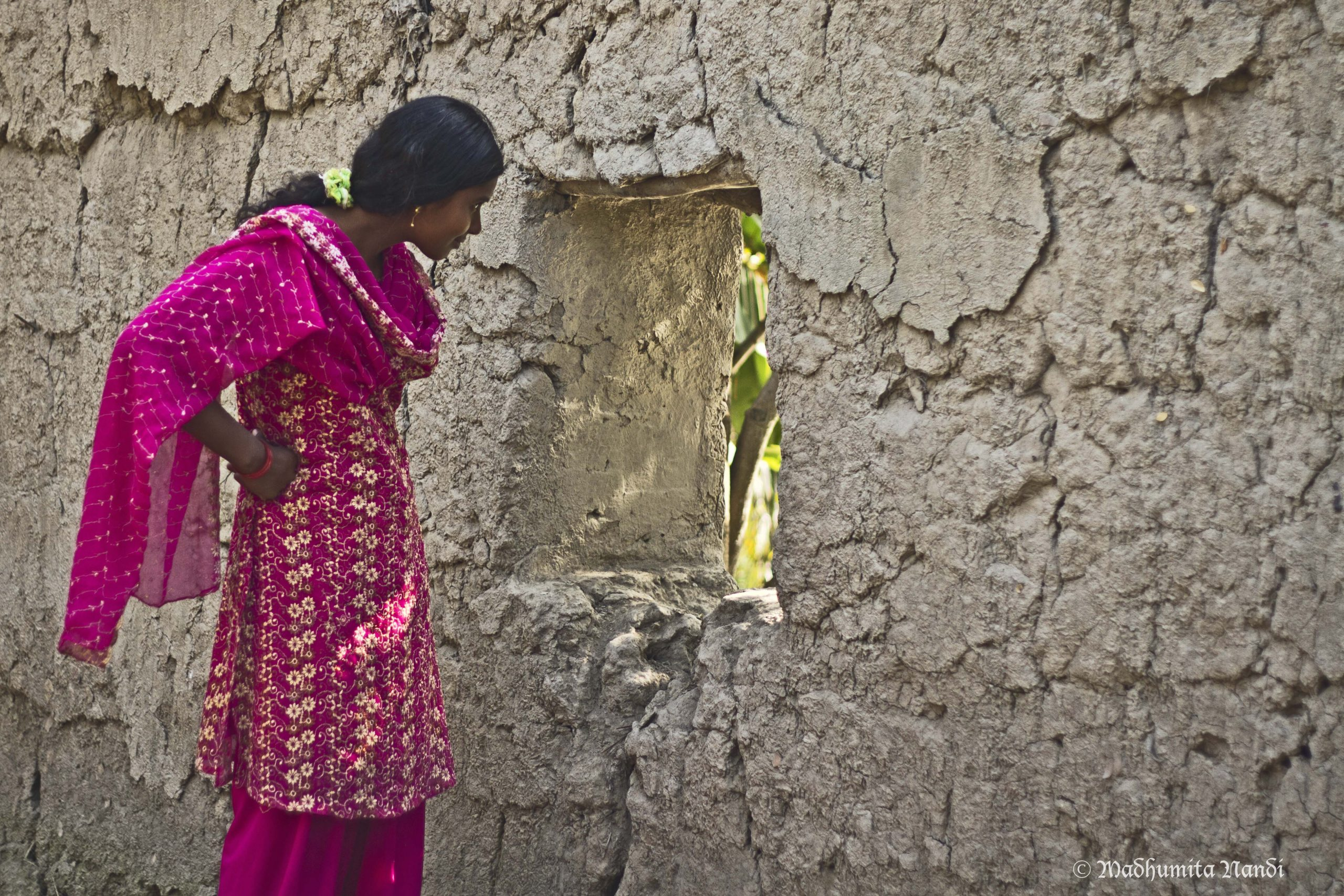 An Indian woman looking outside a window in a wall