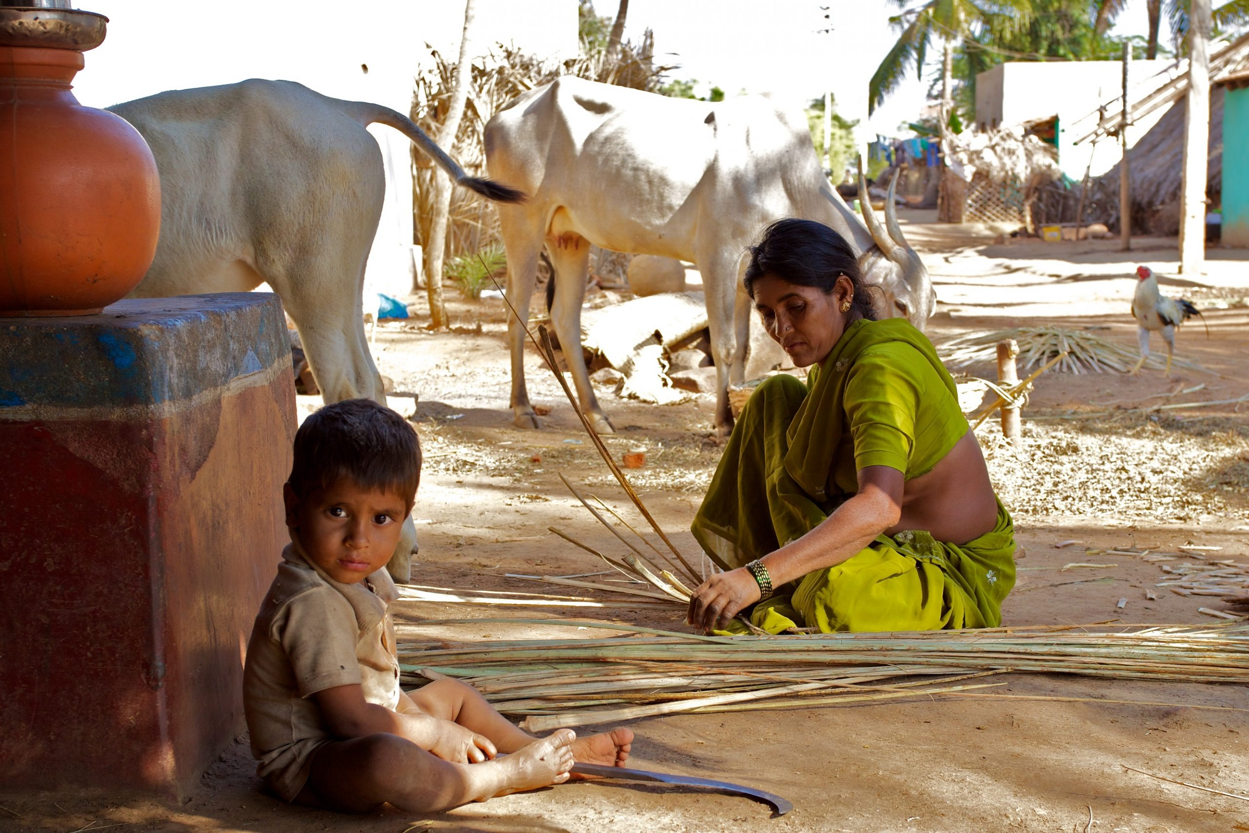 gender inequality_an Indian woman weaving a basket next to her baby