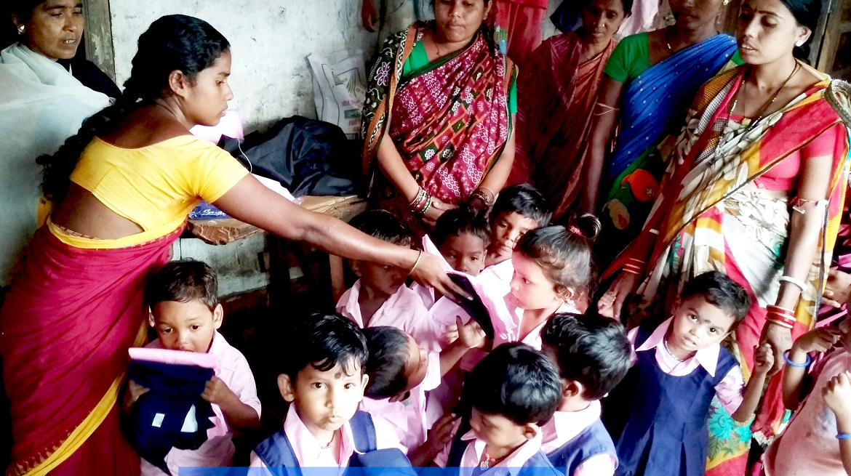 Women distributing uniforms to children