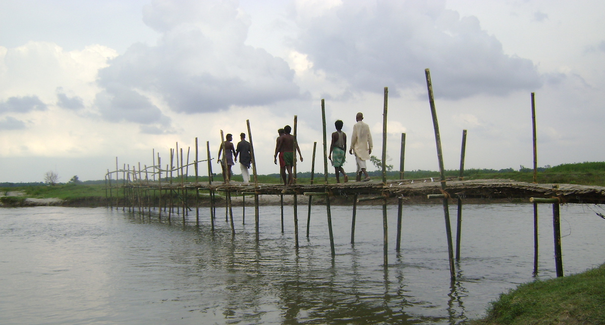 A few men walking on a thin bridge built in the middle of the lake