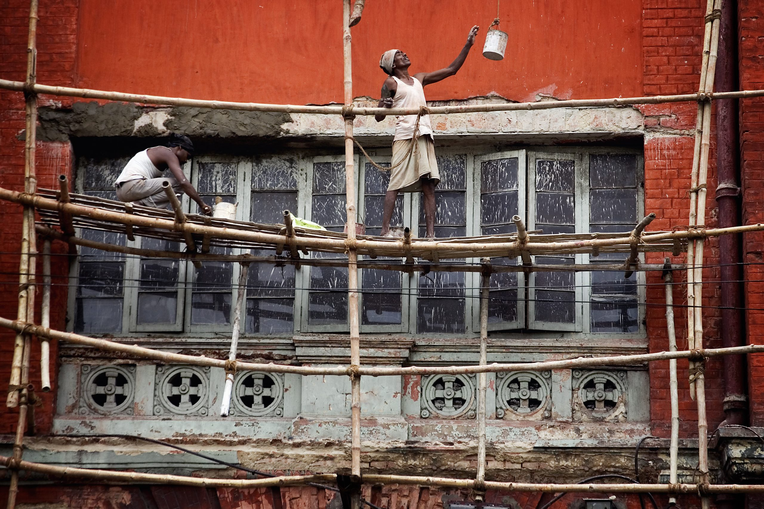 two men on bamboo scaffolding