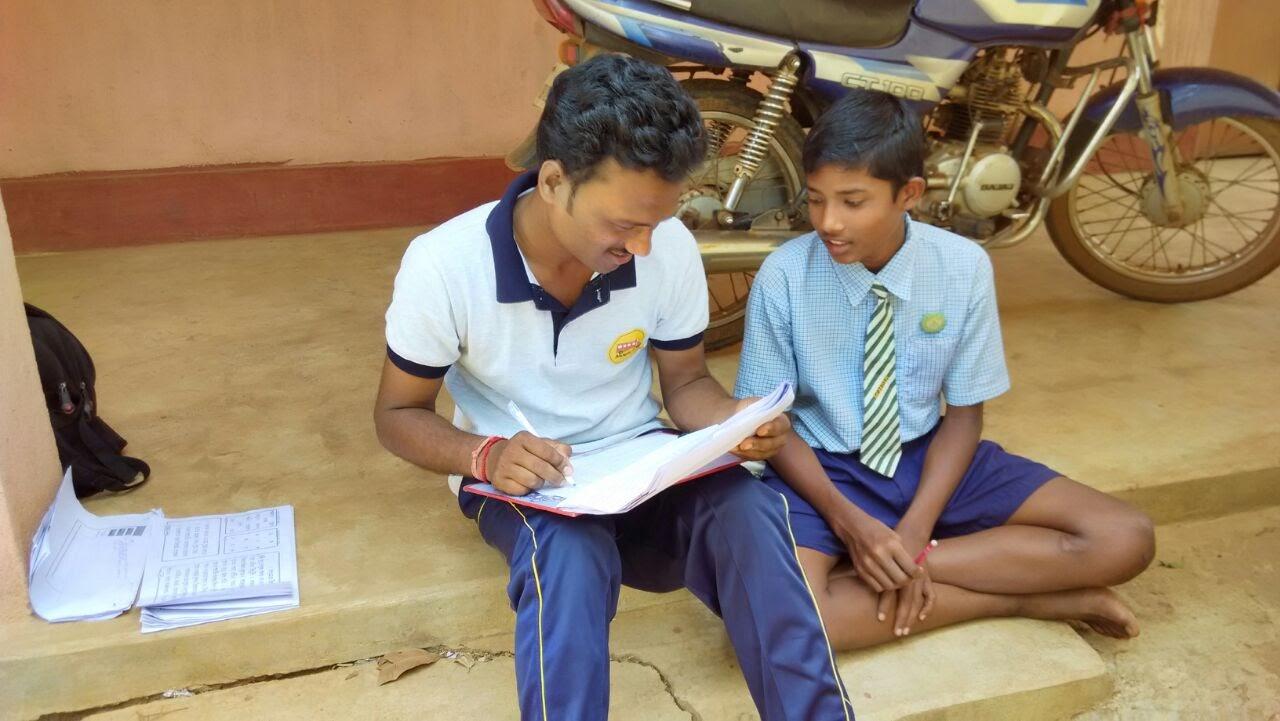 Volunteer teaching something to a village boy