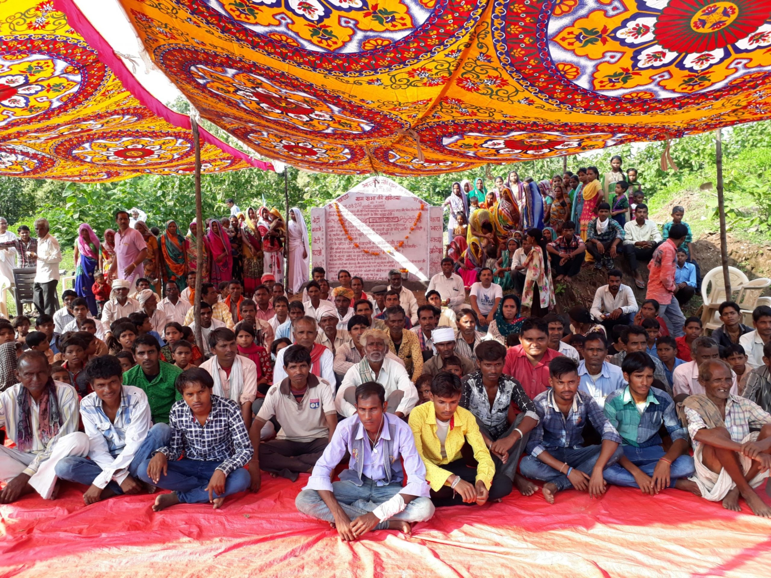 Several villagers sitting under a shade