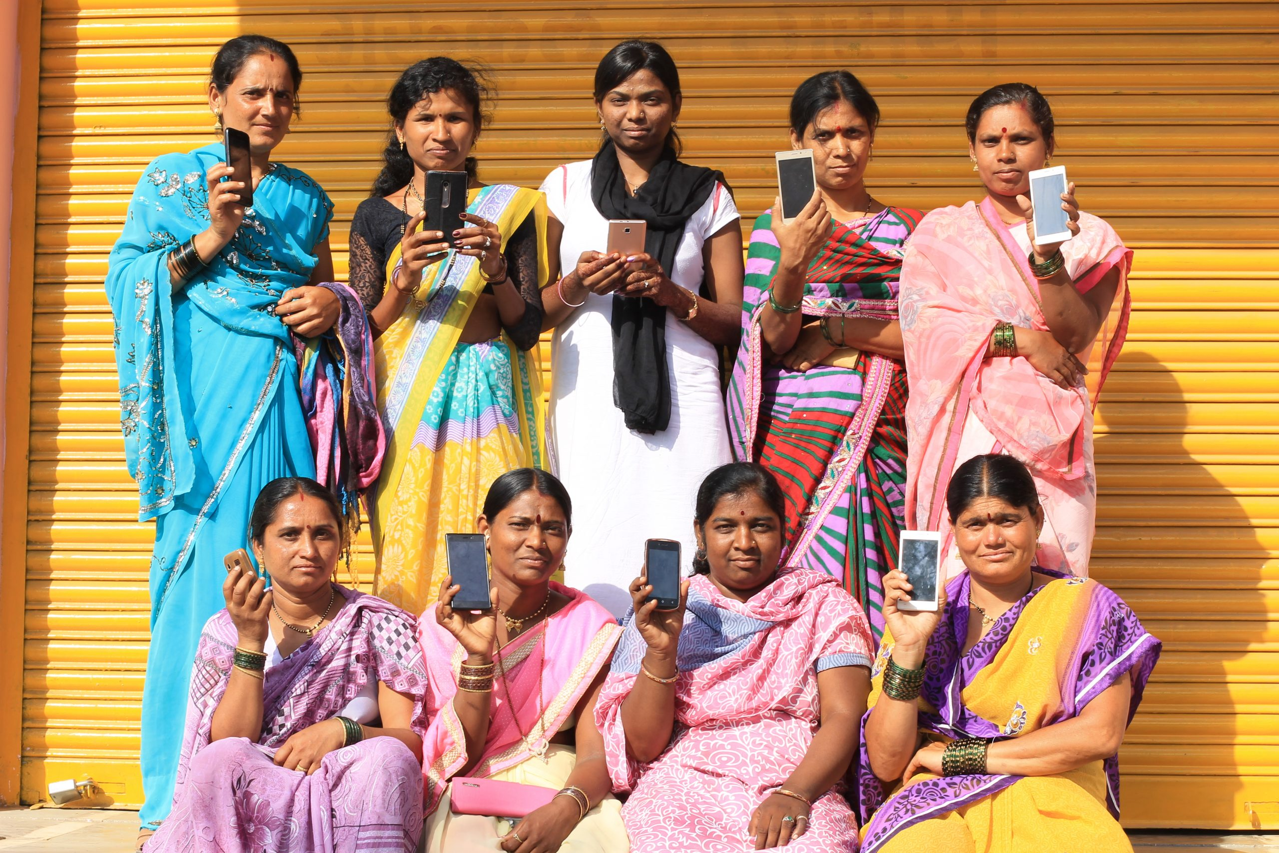 Group of women holding mobile phones_govt schemes_haqdarshak