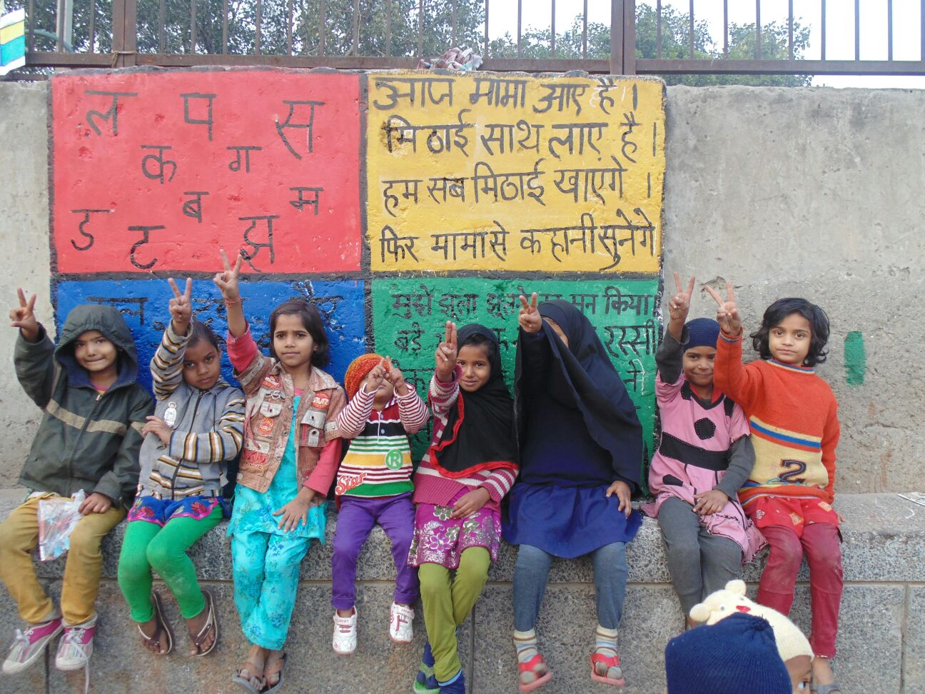 School-going kids in front of brightly painted wall