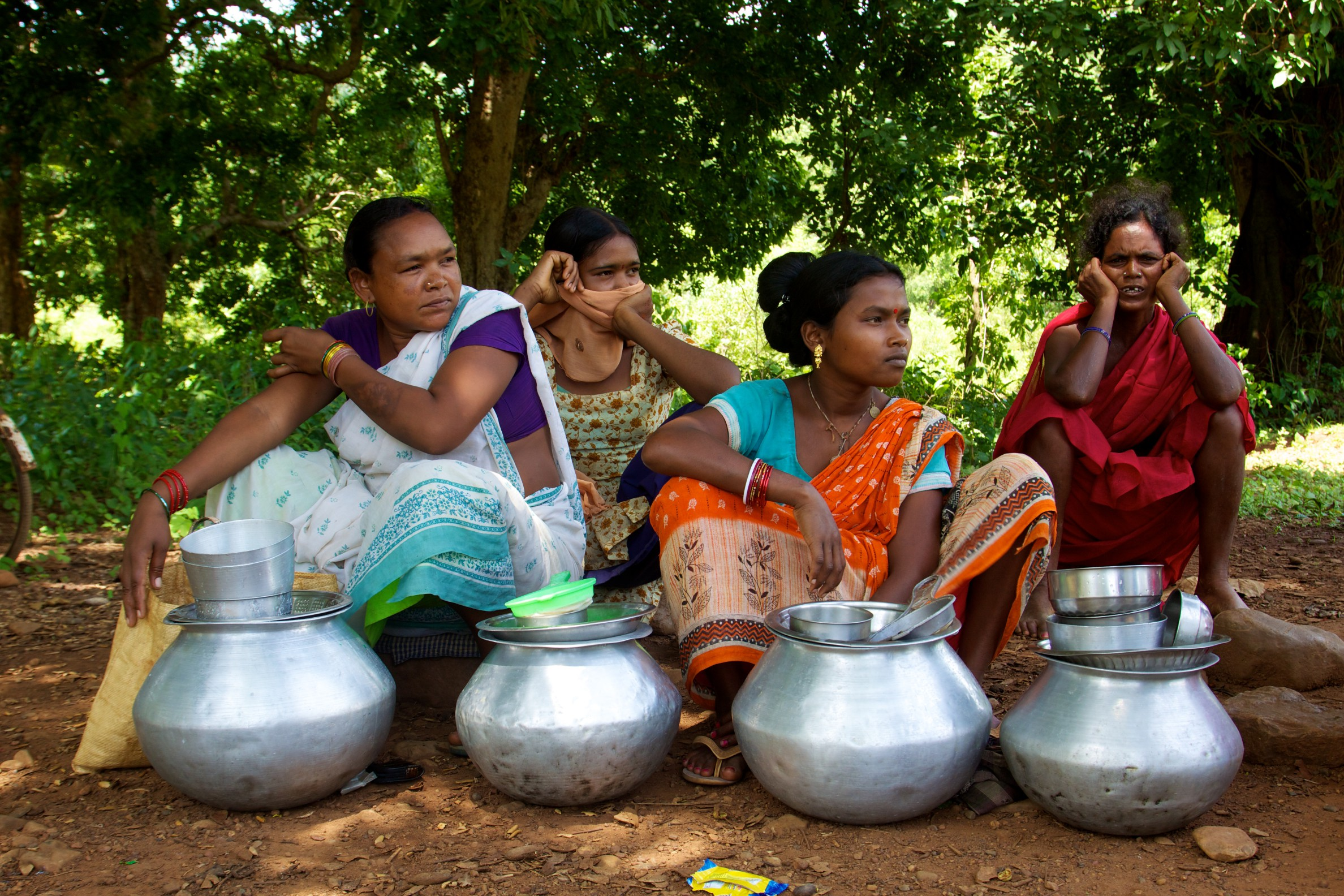 4 women sitting with metal pots