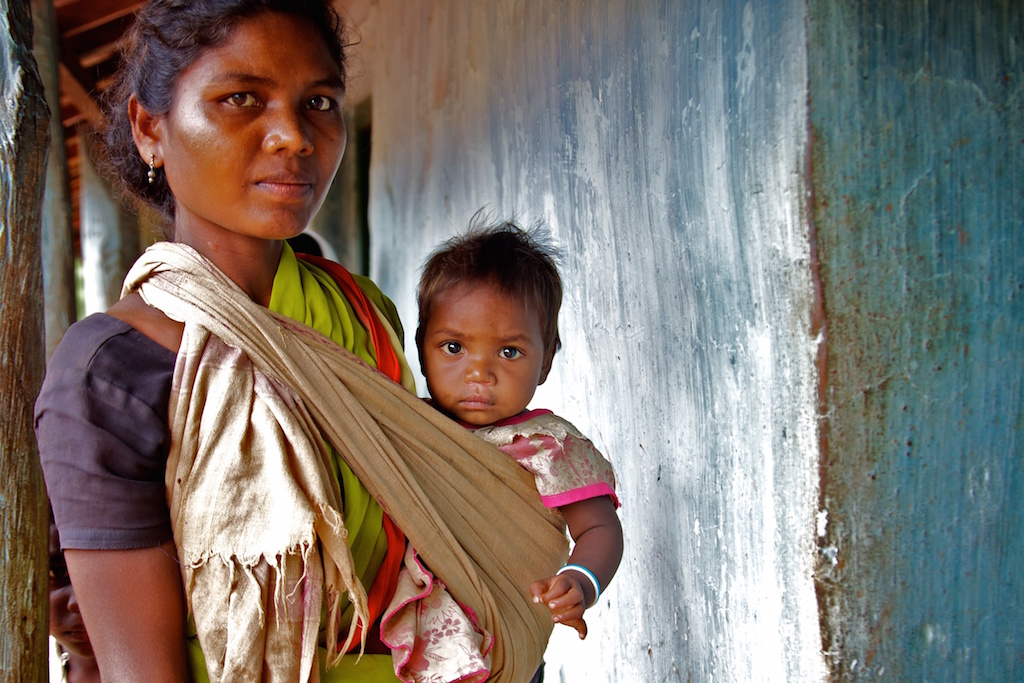 Indian woman carrying infant-maternity benefits