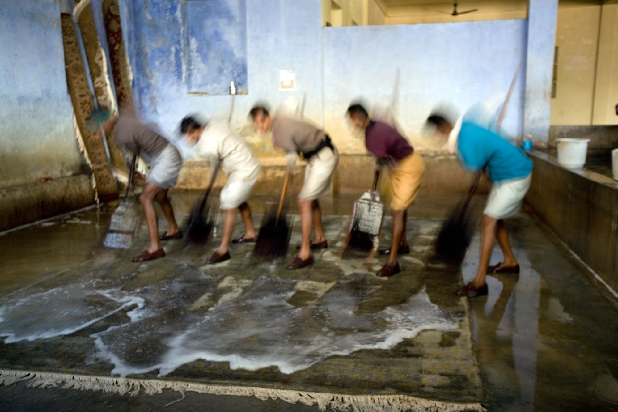 Indian men sweeping rugs