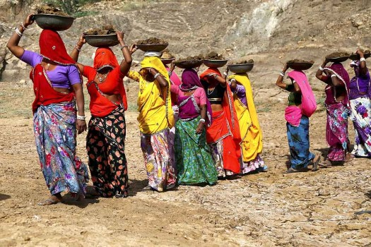 Village women carrying load and walking in a line with their sarees covering their faces