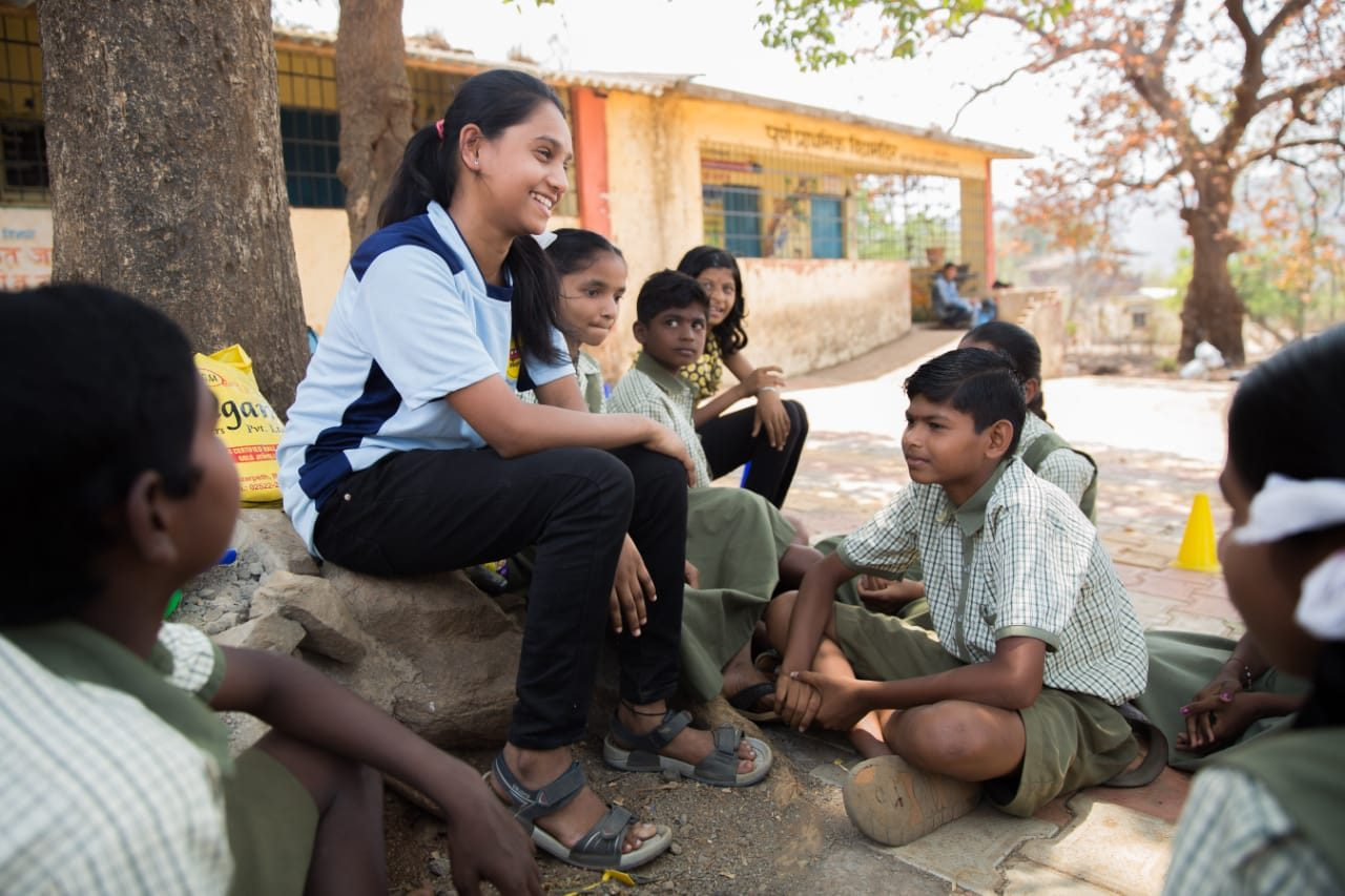 Magic bus teacher sitting with students near a tree - corporates