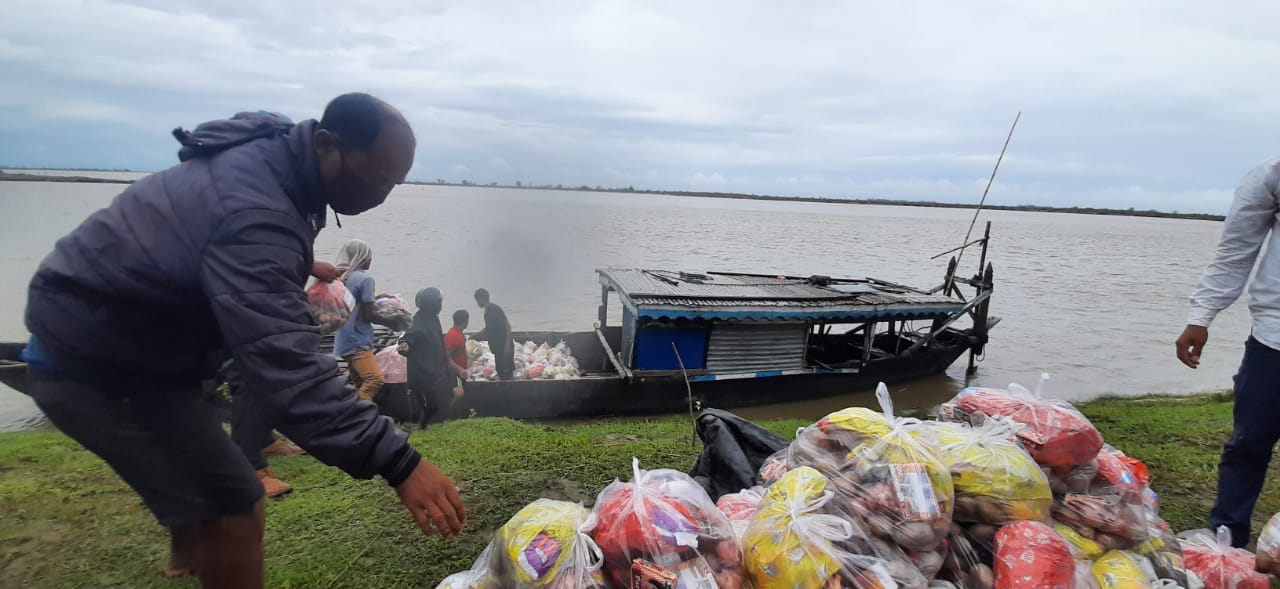 picture of a relief worker standing next to a boat and loading relief material-floods in assam-COVID-19