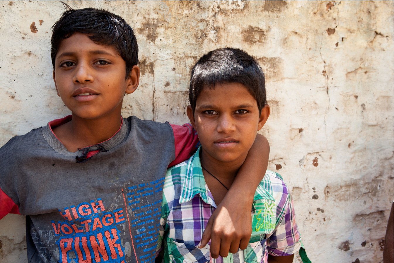 Two young men standing against a wall in India