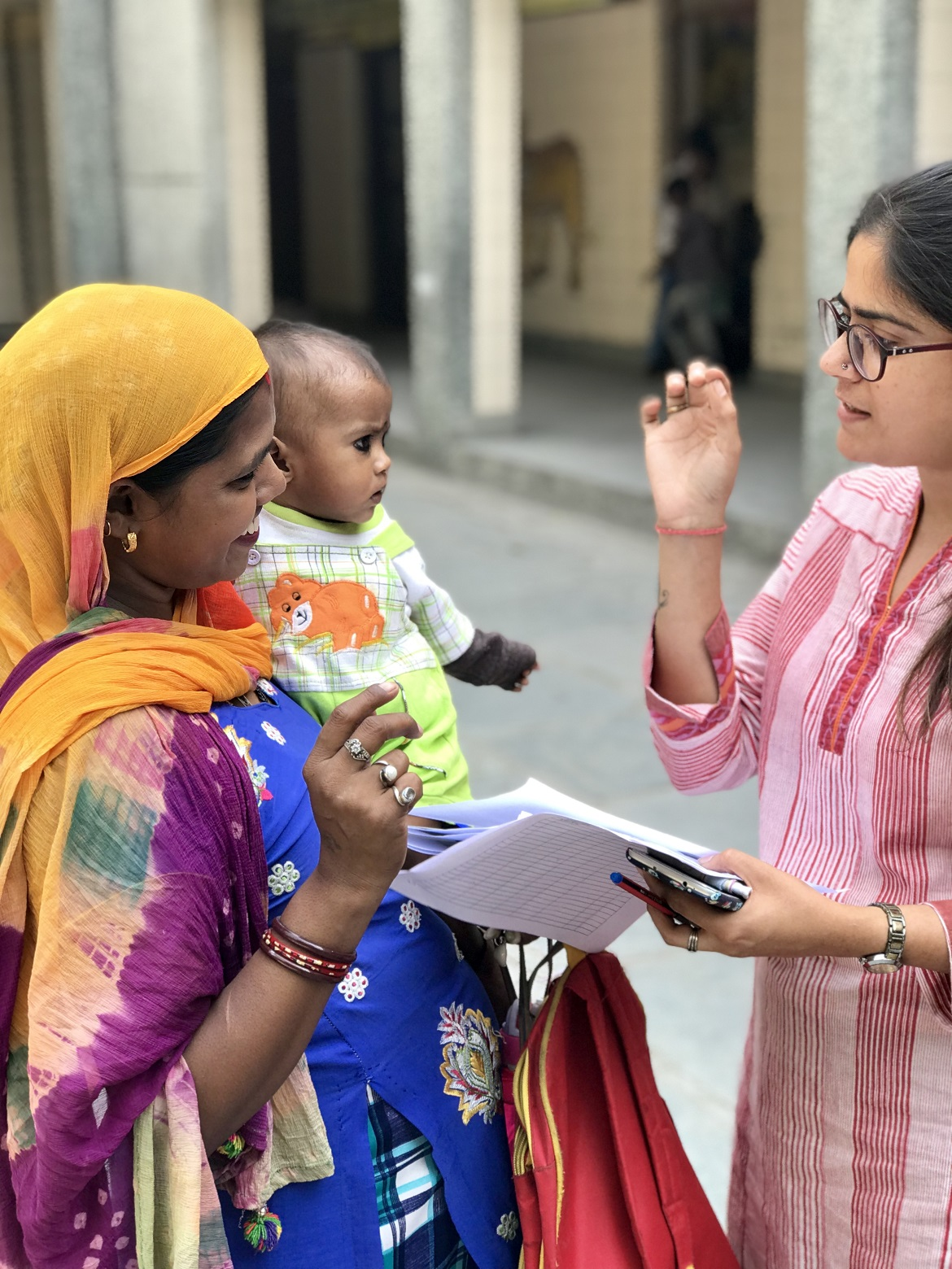 A woman explaining something to a village mother