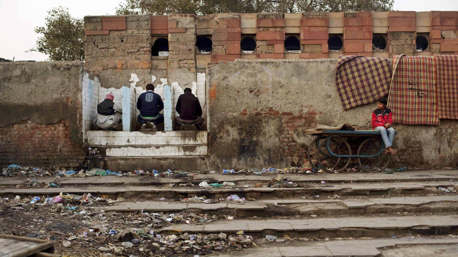 3 men in dirty, open public toilets
