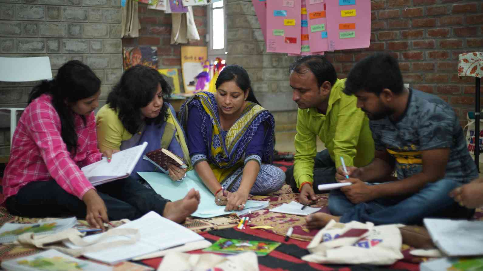 group of five people sitting together at a teacher training session, surrounded by books-teacher training