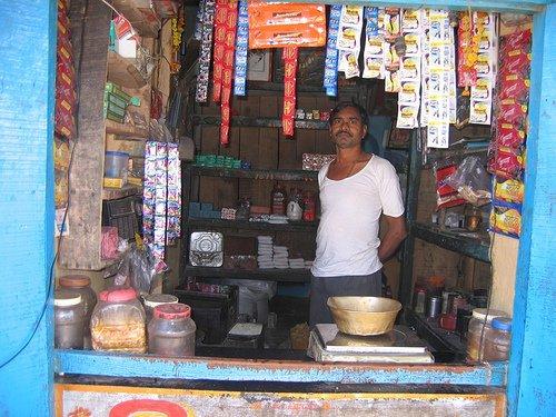 Man wearing white t-shirt in a kirana store