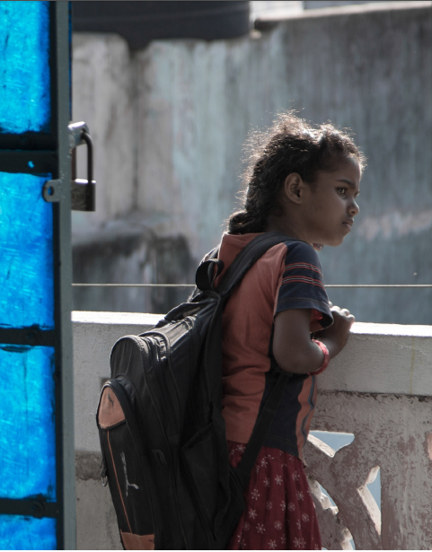 a young girl with a school bag looking out from a terrace