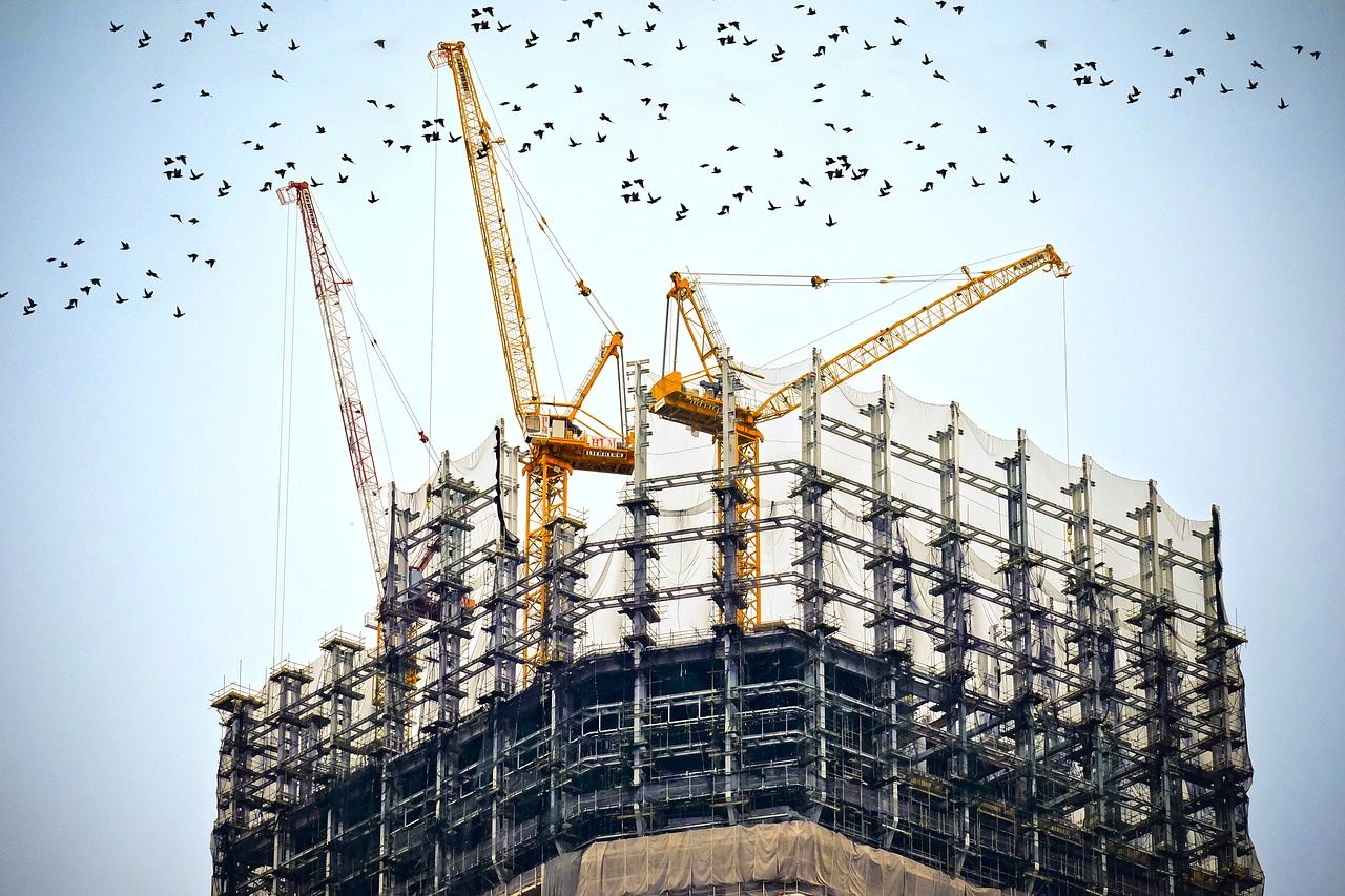 A building under construction in a city with many cranes