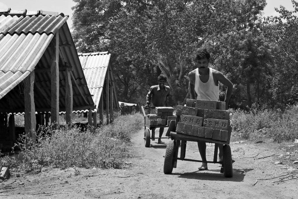two men carrying bricks on a cart