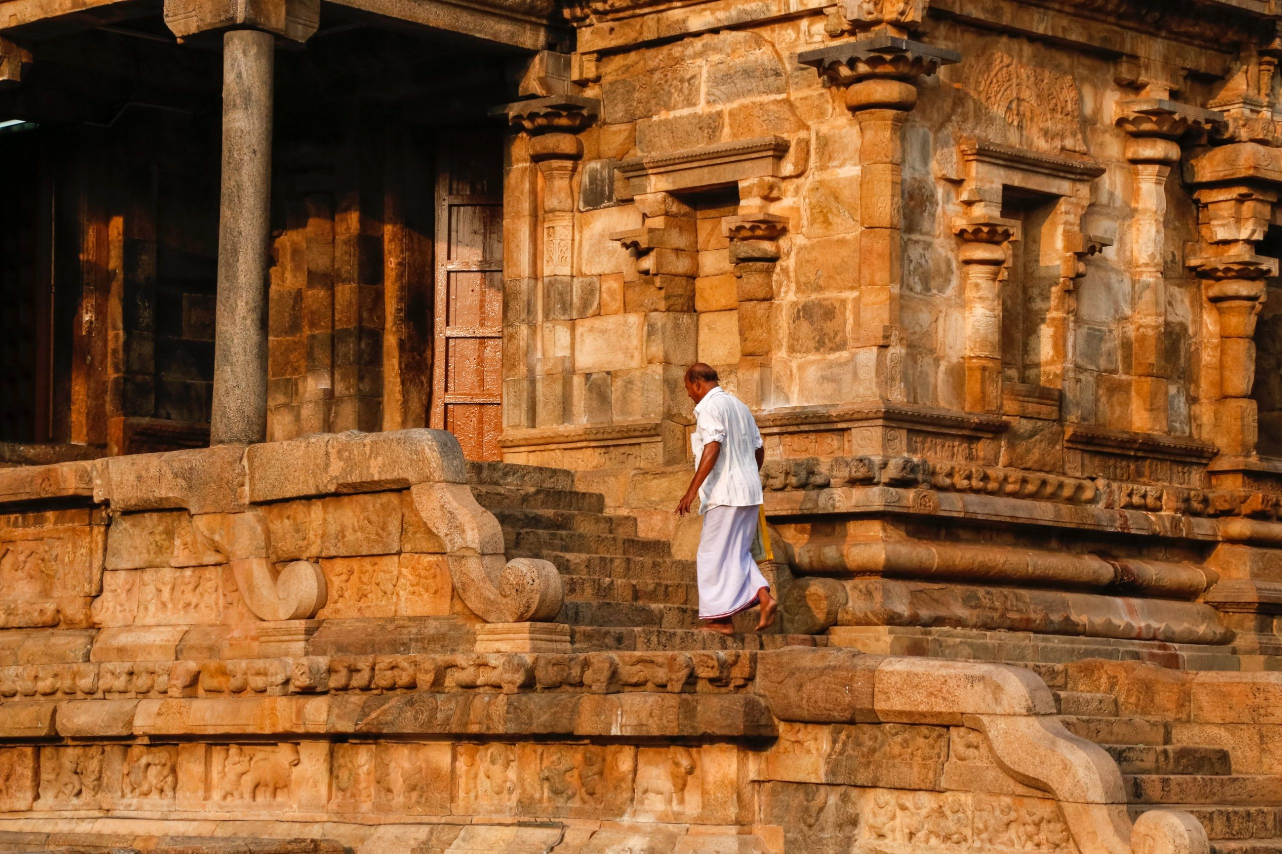 A man walking near a temple/fort
