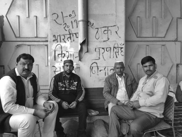 Four people looking into the camera with slogans written on the walls behind them-farmers protest