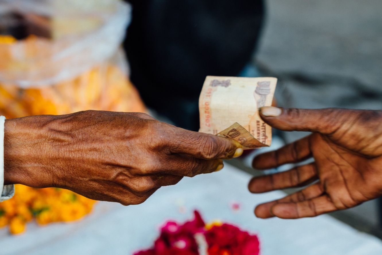 hands exchaging a 10 rupee note_social finance_flickr