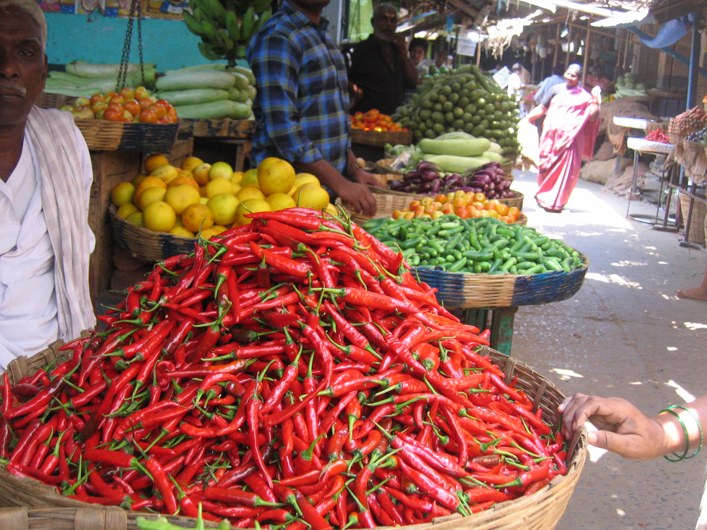 Vegetable market with baskets full of chillies and other vegetables