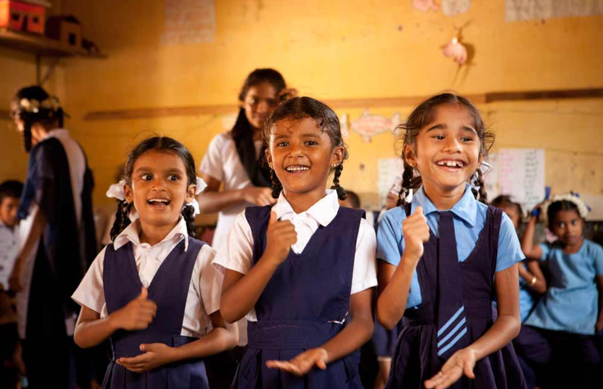 A group of young Indian girls in school uniform playing in a classroom