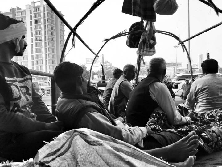 People resting inside a vehicle, looking away from the camera-farmers protest
