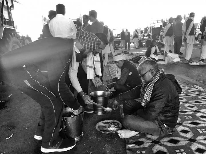 People seated in a row on the ground being served food by people-farmers protest