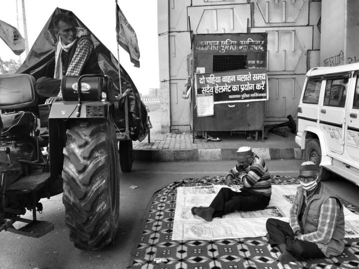 People sitting on a mat in between a tractor and a car-farmers protest
