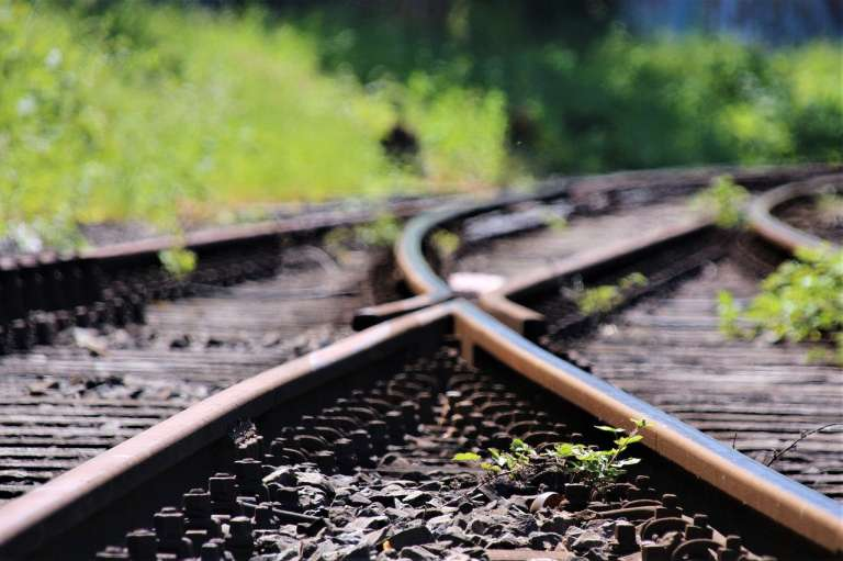 two railway lines intersecting with grass at the side-corruption