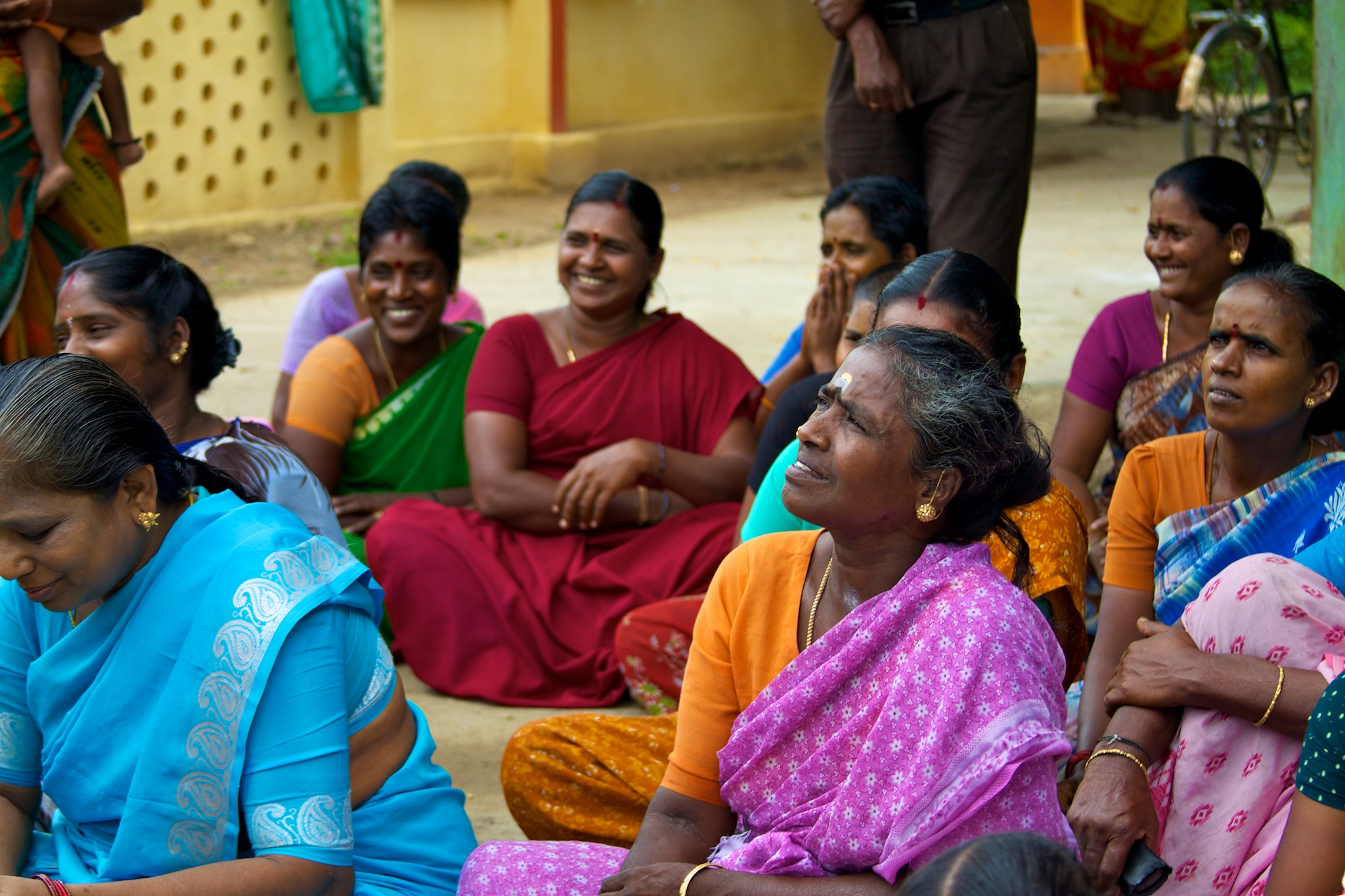 Several women in sarees, talking and laughing