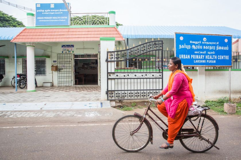 woman cycling past public health centre-healthcare in India
