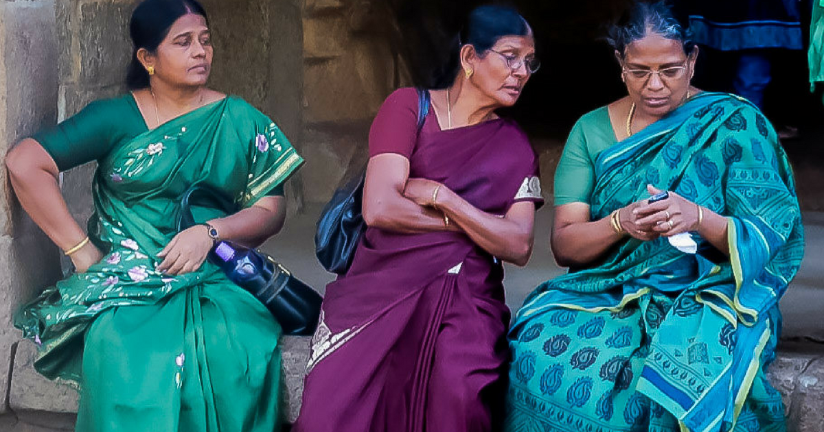 3 women In sarees looking at a phone
