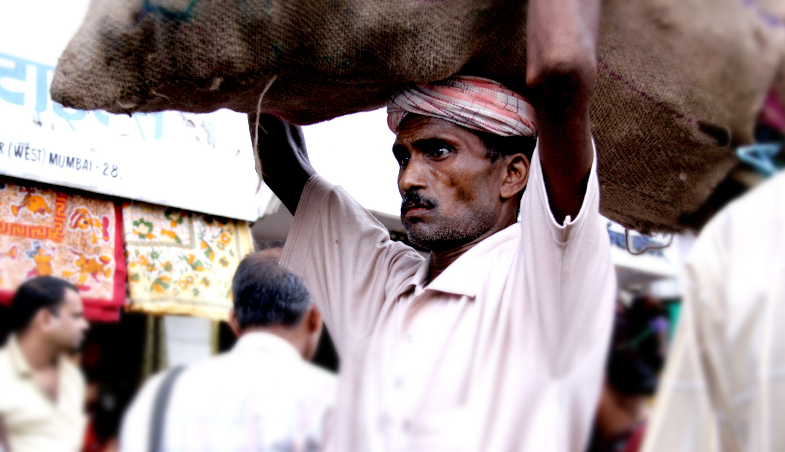 Indian male migrant labourer carrying goods on his head