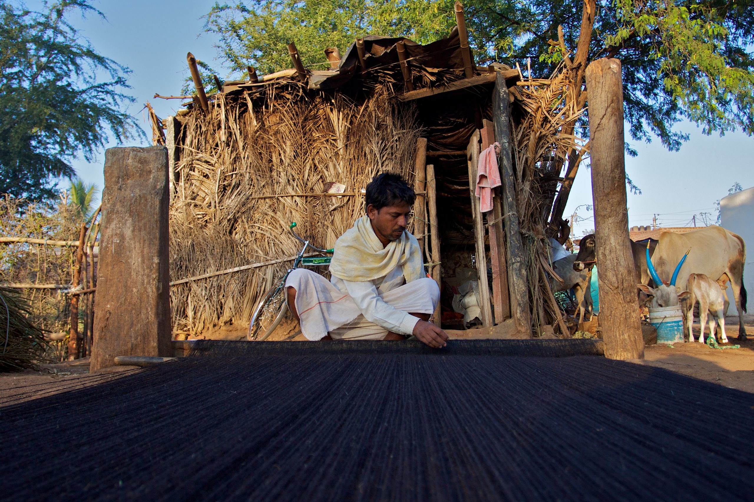 A man in rural India weaving a rug