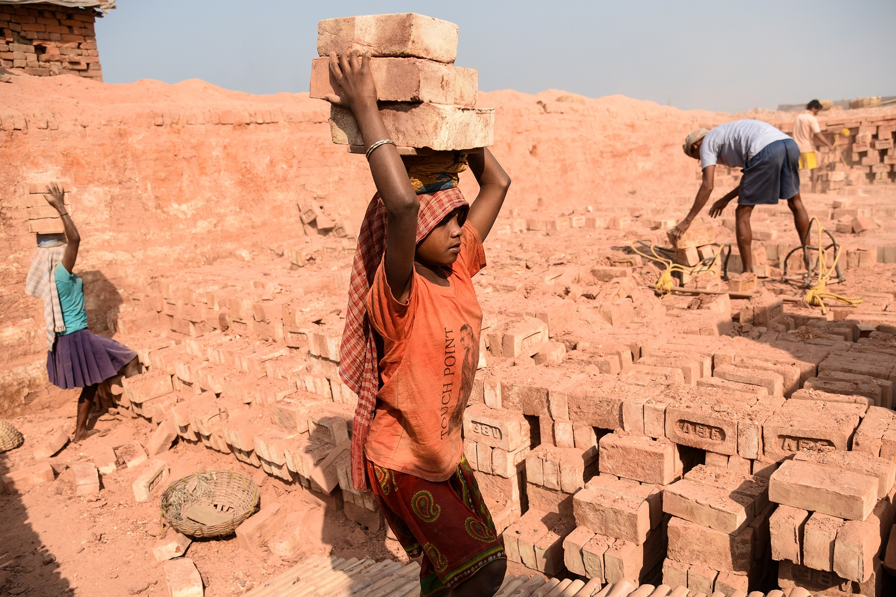 A female child labourer with bricks on her head