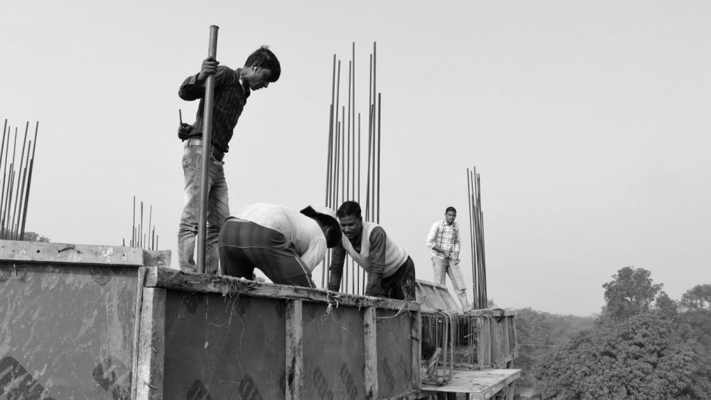 Migrant construction workers in Lucknow casting the roof of the building under construction on site