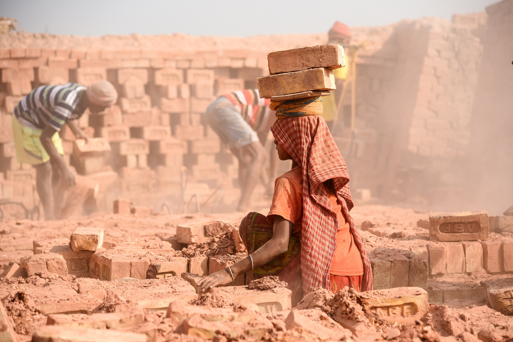 An Indian woman labourer with bricks on her head at the brick kiln