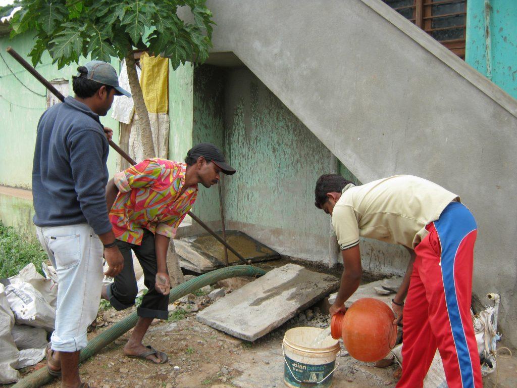 Men pumping a sewage pit_sanitation workers_epw